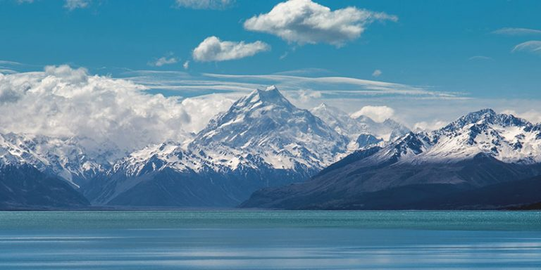 Snow covered peak of Mt Cook with lake in the foreground