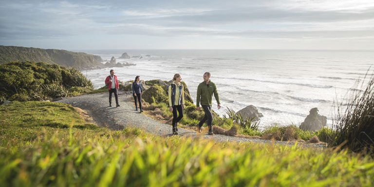 group walking on a track above cliffs overlooking the ocean on a sunny morning