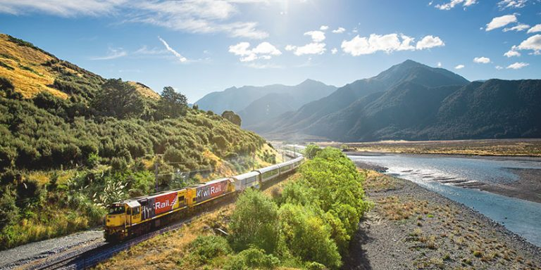 TranzAlpine train on a bend of a rocky river with mountains in the background