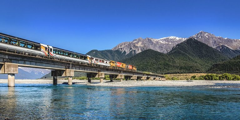 TranzAlpine train crossing a bridge with mountains in the background