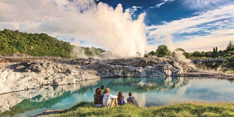group watching geysers in Rotorua geothermal valley