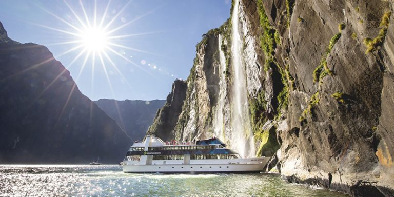 cruise ship approaches waterfall in Milford Sound, Fiordland