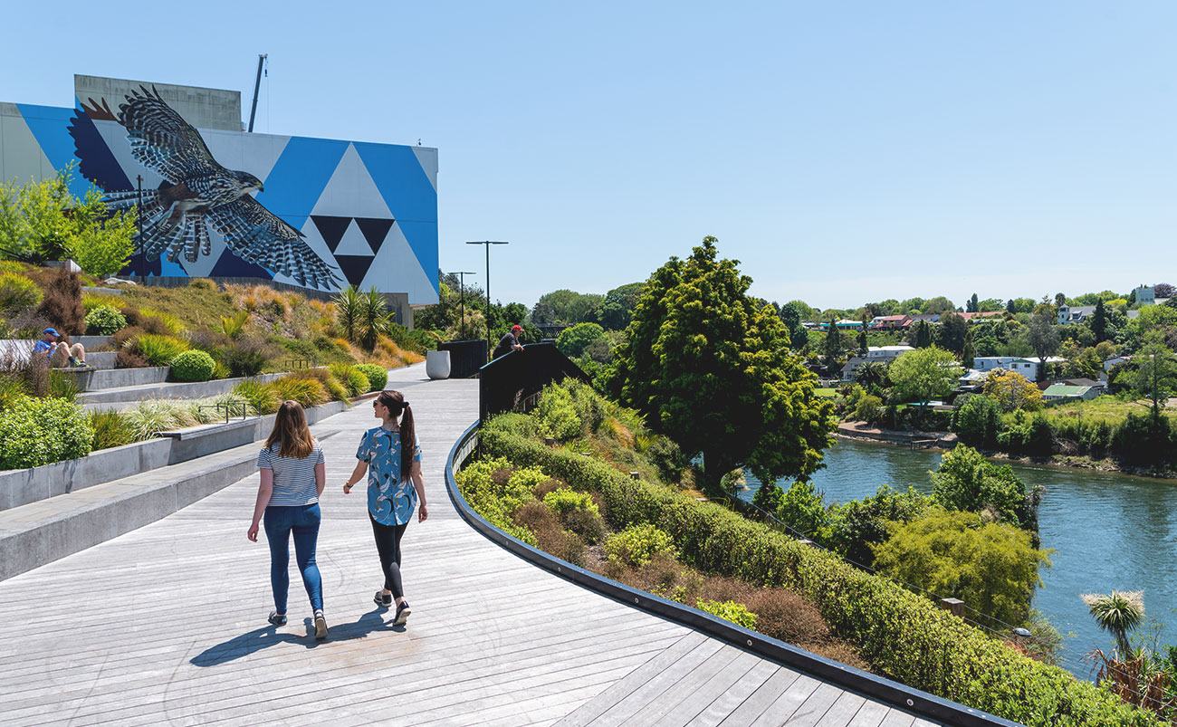 Two women walk along a decked promenade next to the Waikato River in central Hamilton, Waikato, New Zealand