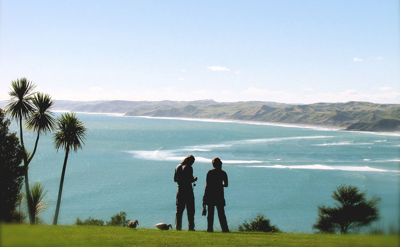 Two people are seen in silhouette as they stand on a green pasture in front of a view of the ocean and black sand beaches of Raglan, New Zealand