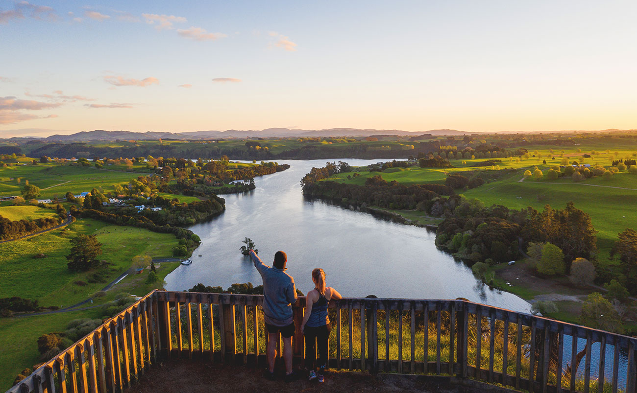 A man and a woman stand on a balcony overlooking the Waikato River as evening sun touches the riverbanks on either side of the river