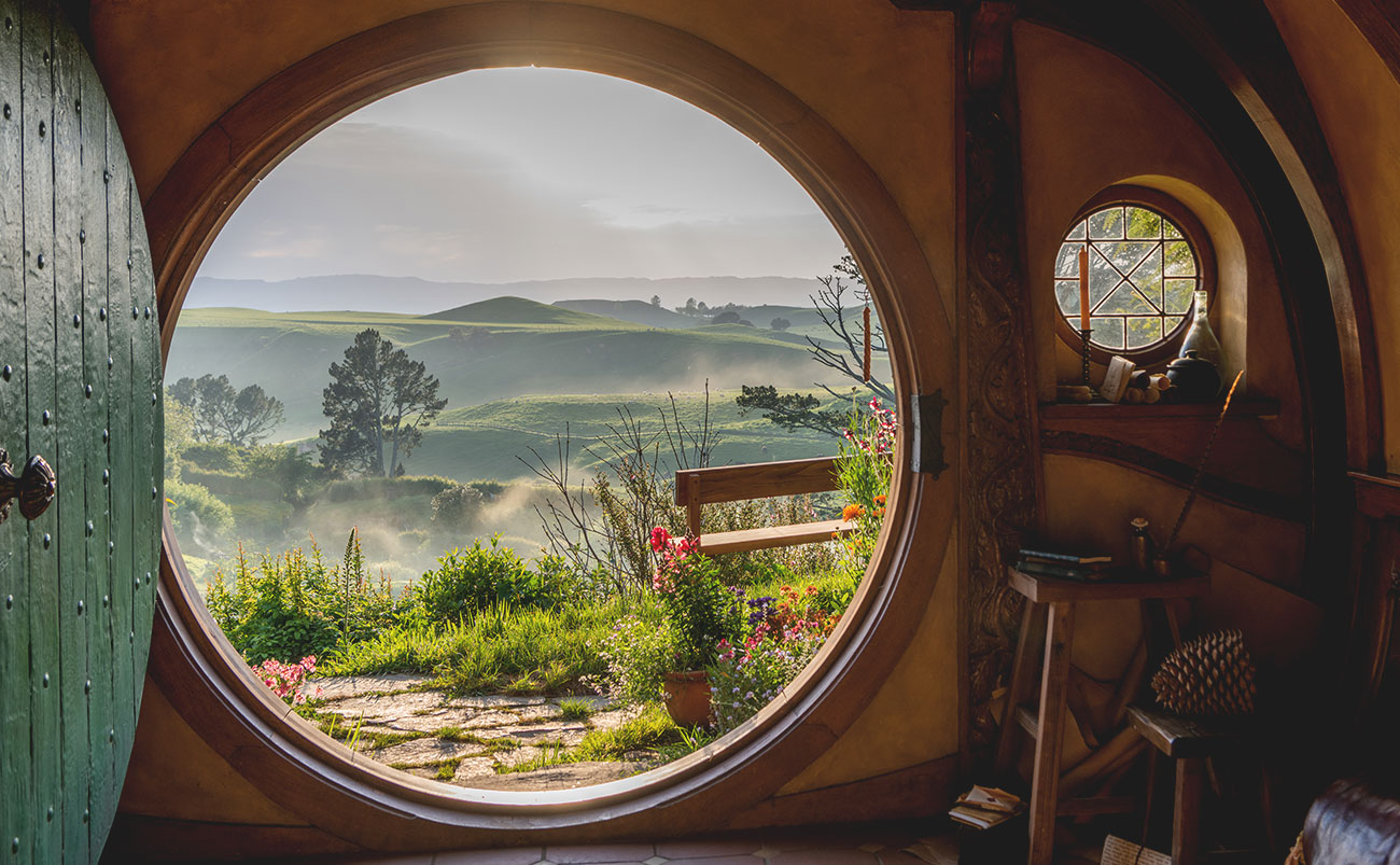 A view over the Hobbiton™️ Movie Set is seen through the circular door of a hobbit hole as morning mist envelops green rolling hills in the near distance